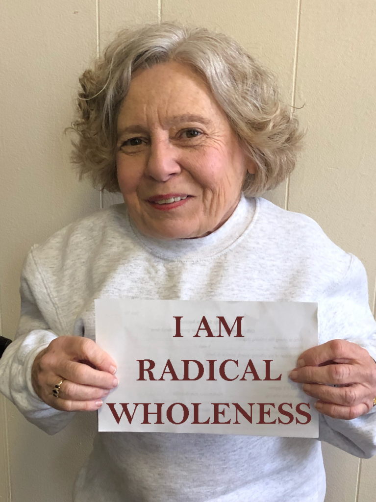 "joy wyler holding a sign that reads ""I am radical wholeness"""